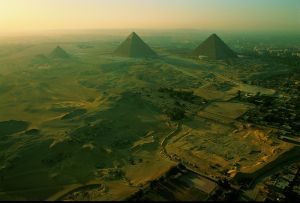 National Geographic Channels International Egypt: Secret Chambers Revealed (c) Ken Garrett   11/01, pg. 84-5 Pay - Cleared for this title only [An aerial view of the Pyramids of Giza.  Excavation in foreground reveals an ancient worksite and cemetery of the builders.]
