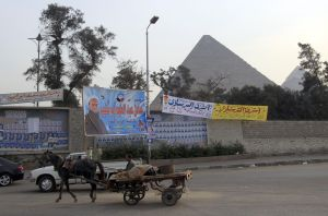 An Egyptian man rides a horse-pulled cart past electoral campaign banners for candidates of the Salafist Al-Nur party near the pyramids of Giza, southwest of Cairo, on December 13, 2011 ahead of the second phase of voting in parliamentary elections. AFP PHOTO/MOHAMMED ABED